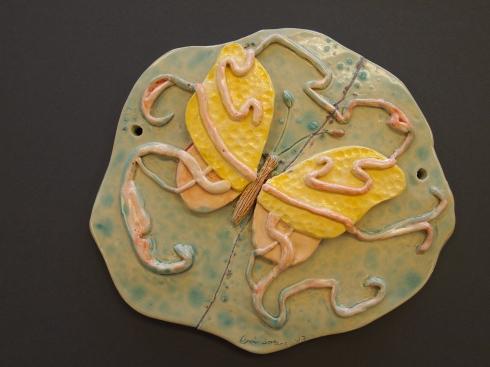 Herkkä perhosreliefi on lasitettu vaalein sävyin.