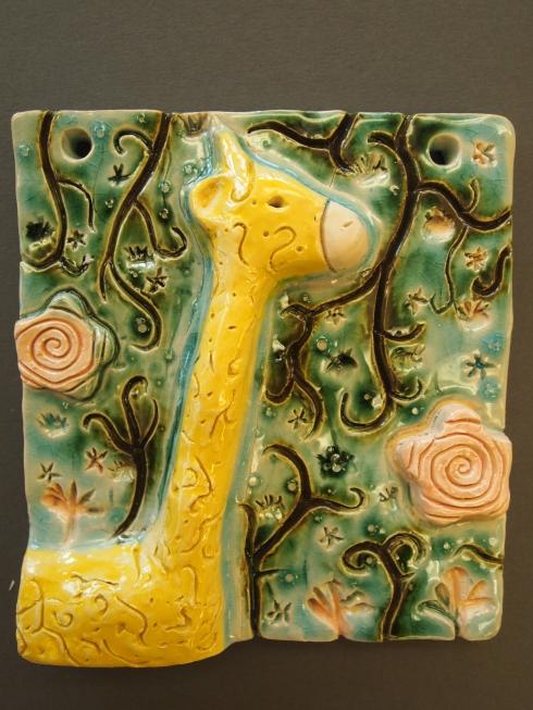 Venlan kirahvi-reliefin taustalla kiemurtelee jugend- tyylistä lainattuja kasviaiheita.
