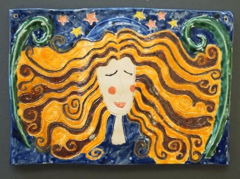 Iloisen reliefin valtaavat oranssit hiukset. Aliisan työssä on taitavaa lasitteiden käyttöä.