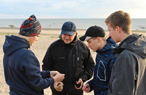 Opettaja Jyrki Autio ja tiedeleirkoululaiset tutkivat kivinäytteitä.